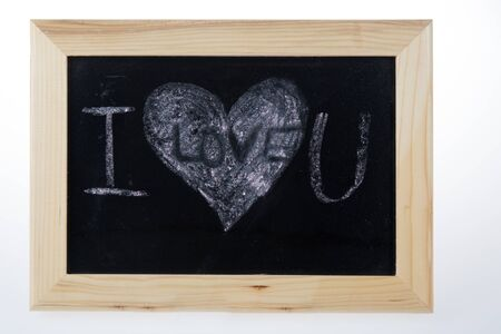 holidays for couples: Wooden board for notes in a heart shape with the words white chalk I love you Stock Photo