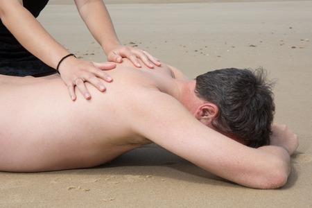40 year old man: Woman putting sunblock on her boyfriends back