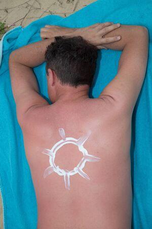 suncream: Applying suncream on the beach with the symbol of sun Stock Photo