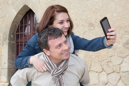trato amable: Tourist Man giving piggy back to a girl and taking selfie holiday