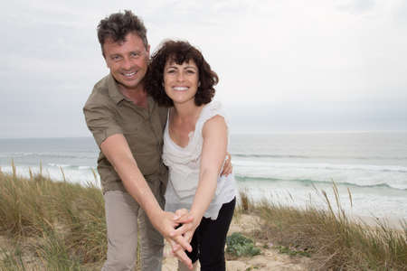 middle age couple: Happy couple hugging on the beach on a sunny day