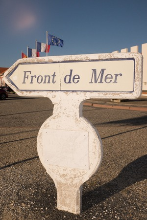 generic location: Street sign written sea front against blue sky
