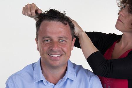 esthetics: Cheerful guy cuts hair at the hair salon by a woman Stock Photo