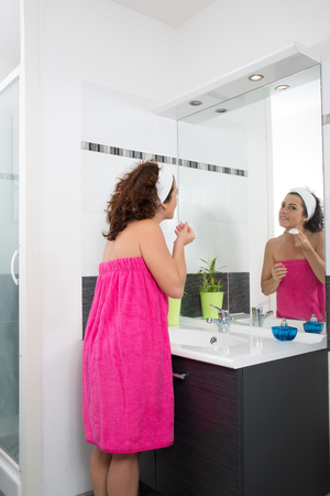 antiaging: Happy woman putting a anti-aging cream on her face