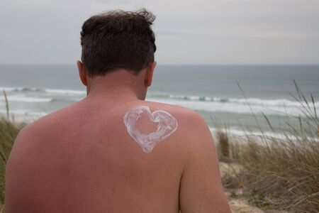 suncare: Man back with sun protection summer day or spring day Stock Photo