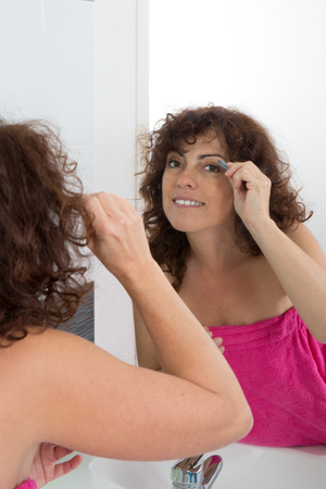 pluck: Woman using tweezers to pluck her eyebrows in front of a mirror in the bathroom