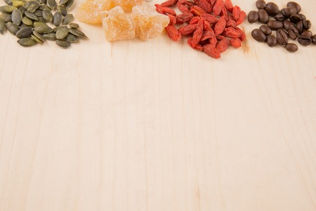 seeds coffee: Goji berries, seeds, coffee, ginger, wooden table with a copy space Stock Photo