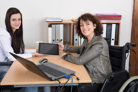 equal opportunity: Business woman shaking hands with disabled colleague at desk in office