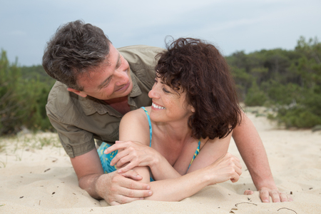 male bonding: Middle-aged couple smiling and happy at the beach on the sand
