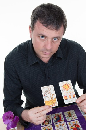 telepathy cards: Man Fortune teller using tarot cards on table