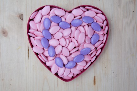 dragees: Heart symbol from chocolate dragees on wooden background, love concept, valentine day
