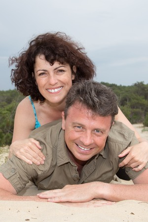 male bonding: Lovely middle-aged couple smiling at the beach on sand Stock Photo