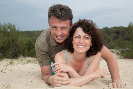 male bonding: Middle-aged couple smiling at the beach on sand