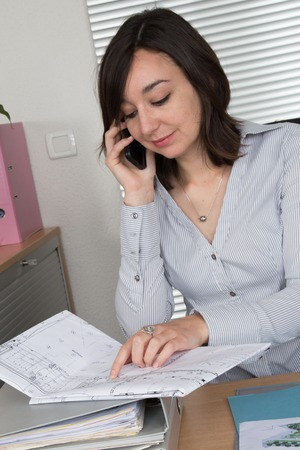 female architect: Young female architect at a desk with blueprints Stock Photo