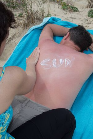 suncare: Woman applying sunblock lotion on a male back at beach