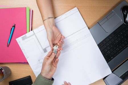 handing over: Close up of female architect hand, handing over house key to a customer. Stock Photo