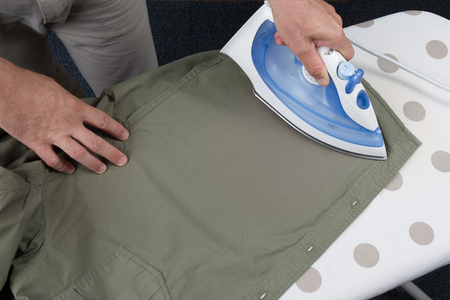 handy man: Hands of man ironing clothes on ironing board Stock Photo