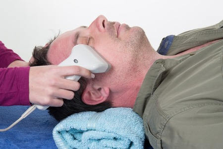 Close-up Of Beautician Giving Laser Epilation Treatment To man Face Stock Photo