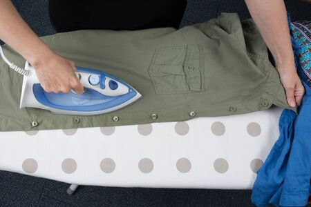 man's shirt: Happy woman Ironing mans shirt with electric Iron Stock Photo