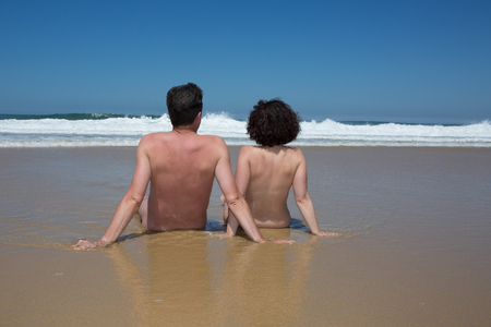 nudism: Nudist couple caucasian man seen from behind relaxing on the seashore
