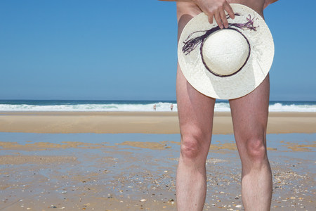 hat nude: Naked man posing with hat nude, on the beach Stock Photo