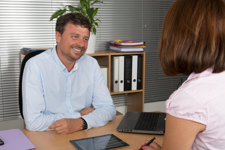 adviser: Two business people talking together at the desk - adviser and customer Stock Photo