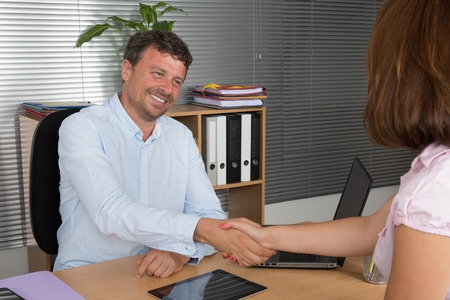 half dressed: Smartly dressed young man and woman shaking hands in a business meeting at office desk