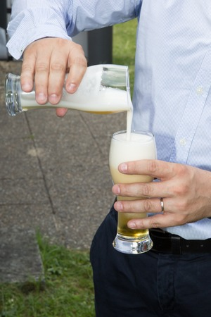bartending: Man pouring beer in a glass outside at summer Stock Photo