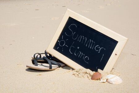 swim shoes: Summer time written on a chalkboard at the beach
