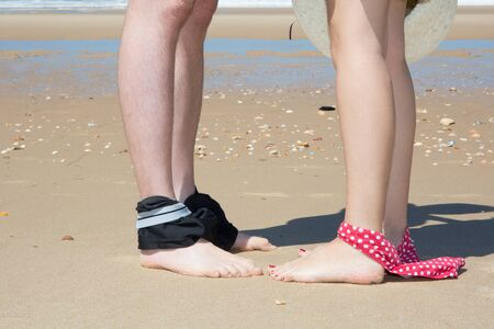 waist down: Legs of couple at the sea with bikini down and hat under blue sky