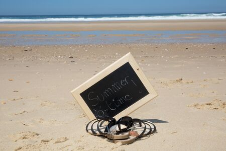 swimming shoes: Summer time written on a chalkboard at the beach
