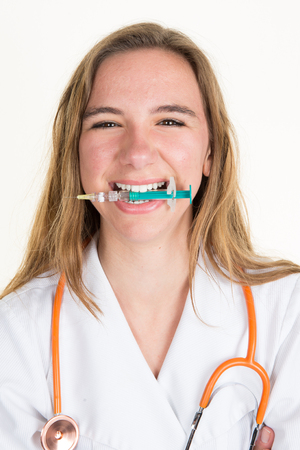 Girl doctor biting a syringe with a needle isolated Stock Photo