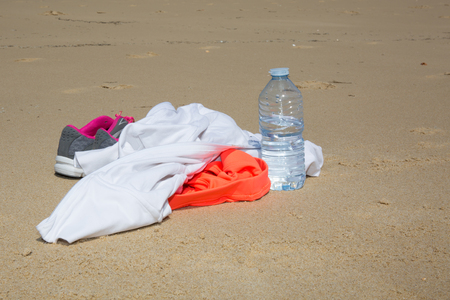 pair ofsports gym shoes on a sand with water and shirt