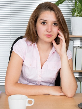 Business woman looking in camera while leaning on desk