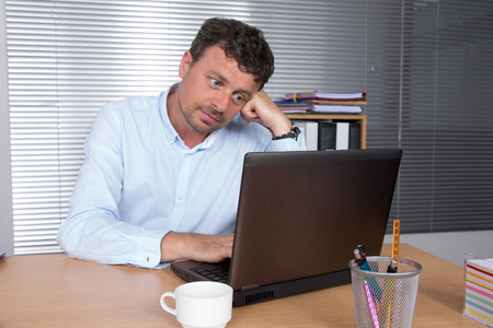 fed up: Serious doubtful businessman thinking and looking sideways sitting in a desk at office