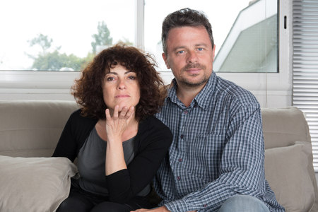 middleaged: Middle-aged couple relaxing on sofa at home