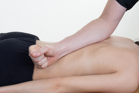 back sprains: Doctor massaging the back of his patient while using the back of his hand in a room