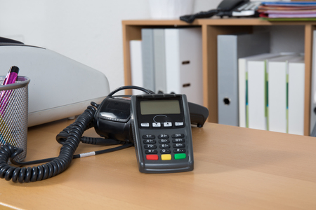 compute: Close up of Credit Card Reader and Cash Register on background of store