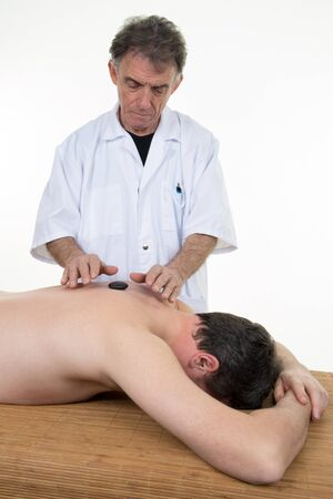 Man having a massage in a wellness center by therapist Stock Photo
