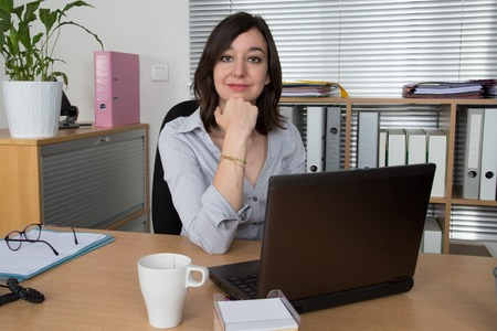 ultrabook: Portrait of businesswoman with laptop writes on a document at her office