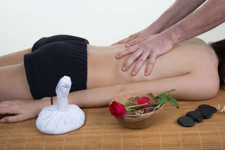 massaged: Young beautiful caucasian woman lying on a massage table and is being massaged. Isolated on white.
