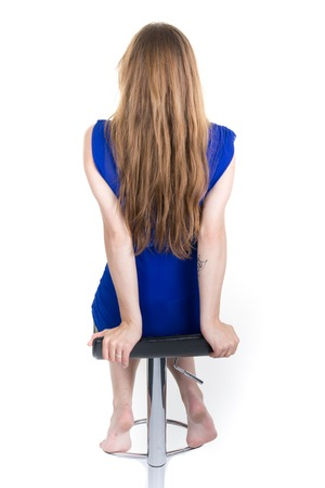 Blond woman long hair white background blue dress sitting on chair back view