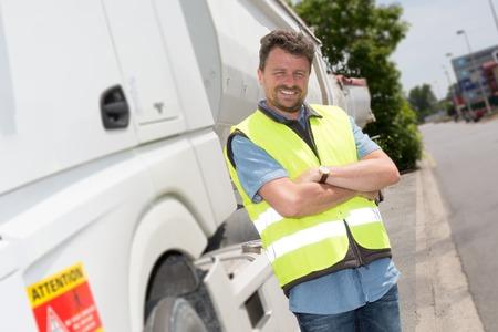 Proud bestuurder of expediteur in de voorzijde van trucks en trailers op een overslagplaats Stockfoto