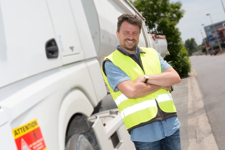 Proud driver or forwarder in front of trucks and trailers, on a transshipment point Standard-Bild