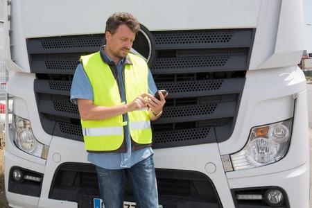 conductor orgulloso o promotor en frente de camiones y remolques, en un punto de transbordo Foto de archivo