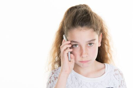 short wave: Little girl angry, talking on mobile phone. Studio photography, 10 years. Stock Photo