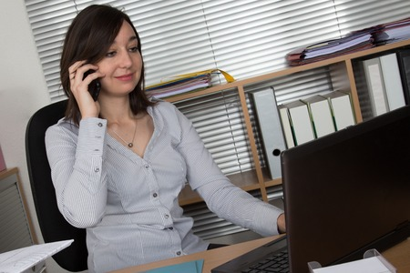 important phone call: Smiling young business woman on phone on laptop at office