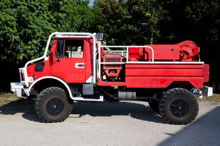 under fire: coche de bomberos rojo en un hermoso día de verano bajo el fondo verde Foto de archivo