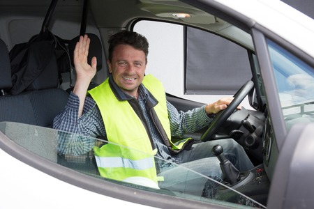 Smiling construction worker driving a car, say hello while driving car.