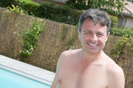 perfect teeth: Close up portrait of a handsome and happy mid aged man relaxing in swimming pool smiling with perfect teeth.